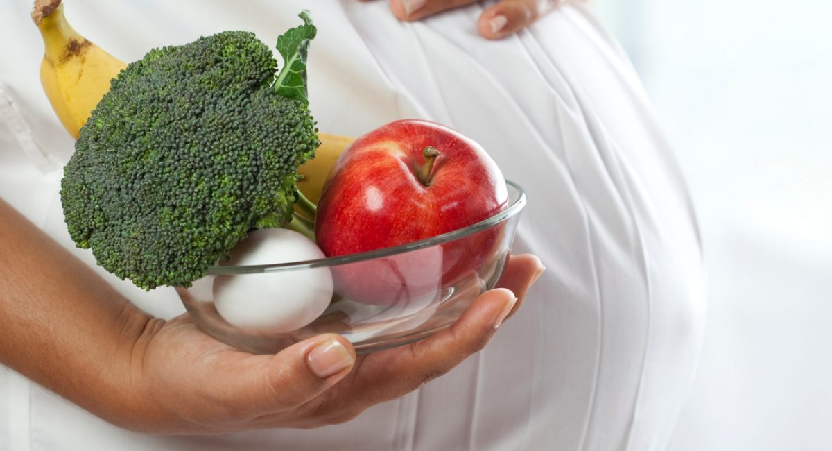 """""""A pregnant woman with pregnancy superfoods such as broccoli, apples, bananas and eggs. You may also like:"""""""